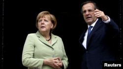 Greek Prime Minister Antonis Samaras talks with German Chancellor Angela Merkel in Athens.