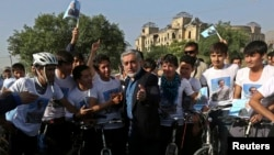 Afghan presidential candidate Abdullah Abdullah talks with a group of cyclists in Kabul on June 6.