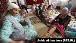 Бесік тойында немересінің жанында отырған әже. Рахат ауылы, Науаи облысы, Өзбекстан, 6 маусым 2015 жыл. Көрнекі сурет.
