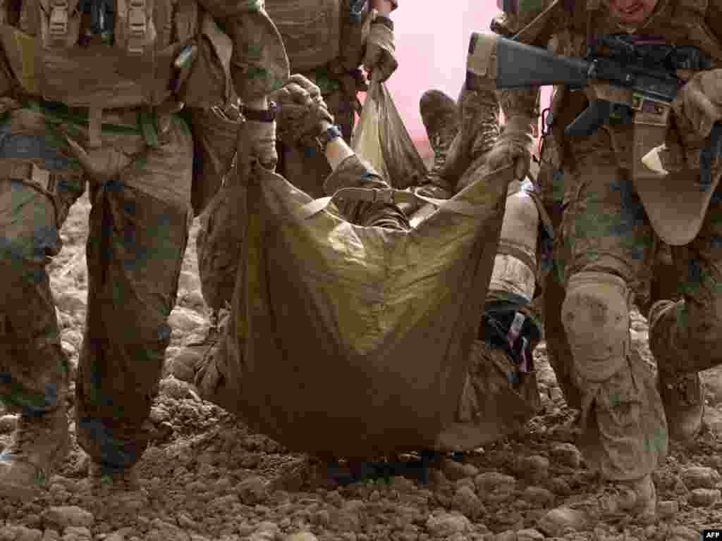 U.S. Marines carry a comrade wounded by an improvised explosive device to a medevac helicopter in Afghanistan's Helmand Province. (Photo for AFP by Behrouz Mehri)