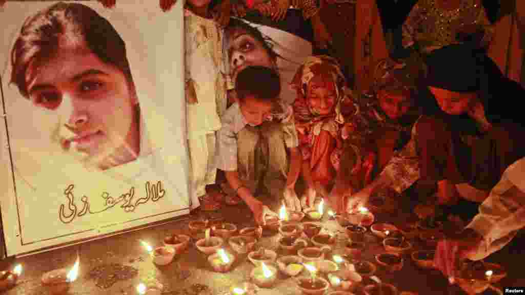 OCTOBER 12, 2012 -- Children light oil lamps at a Peshawar school beside a picture of 14-year-old Malala Yousafzai, who was gunned down three days earlier by Taliban attackers for speaking out against militants and promoting education for girls. (REUTERS/Athar Hussain)