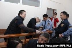 В центре в белой шапочке инвалид второй группы по зрению подсудимый Оралбек Омыров, для которого прикованный к нему полицейский служит своего рода и поводырем. Алматы, 4 октября 2018 года.