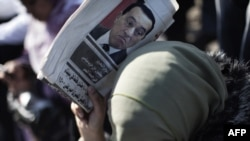 A woman shields herself from the sun with a newspaper bearing a portrait of deposed President Hosni Mubarak during celebrations on Cairo's Tahrir Square on February 18.
