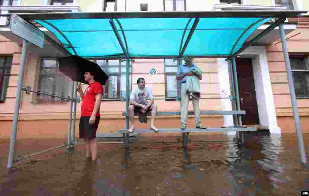 People wait for at a flooded bus stop during heavy rain in Minsk on August 12. (AFP/Sergei Gapon)