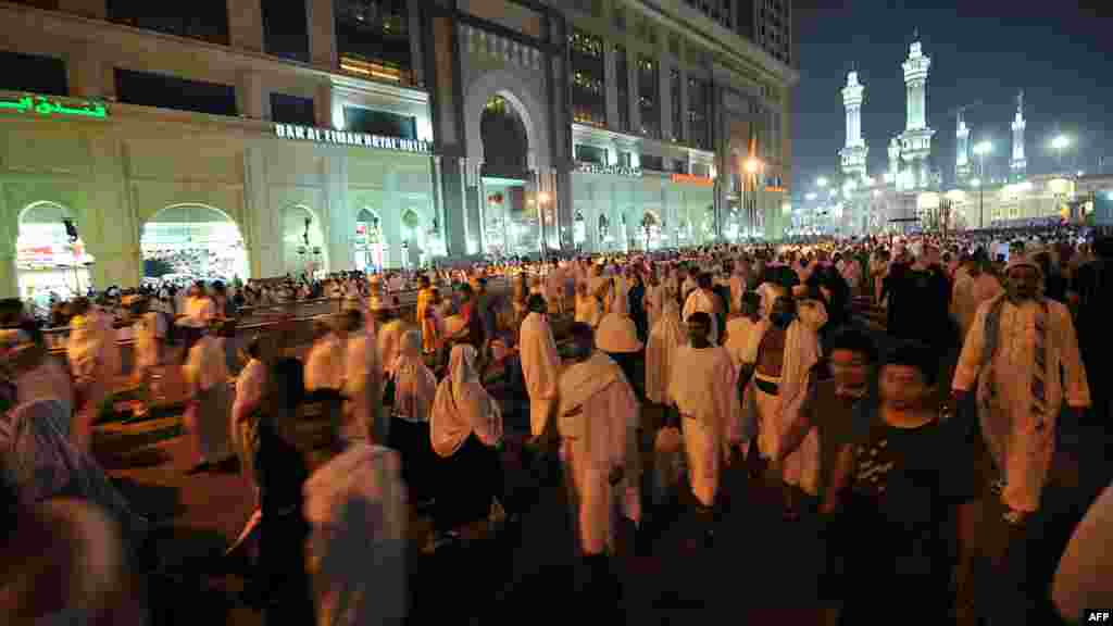 Pilgrims leave the area of the Grand Mosque, seen in the background, following evening prayers during the hajj. (AFP PHOTO/FAYEZ NURELDINE)
