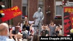 MLPD leader Gabi Fechtner (right, in gray) sings the Internationale next to the Lenin monument.