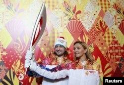 Ресейлік спортшылар Татьяна Навка (оң жақта) мен Илья Авербух олимпиада алауын ұстап тұр. Мәскеу, 14 қаңтар 2013 жыл.