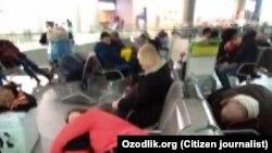 Аэропортда чартер рейсни кутаётган ўзбекистонликлар.