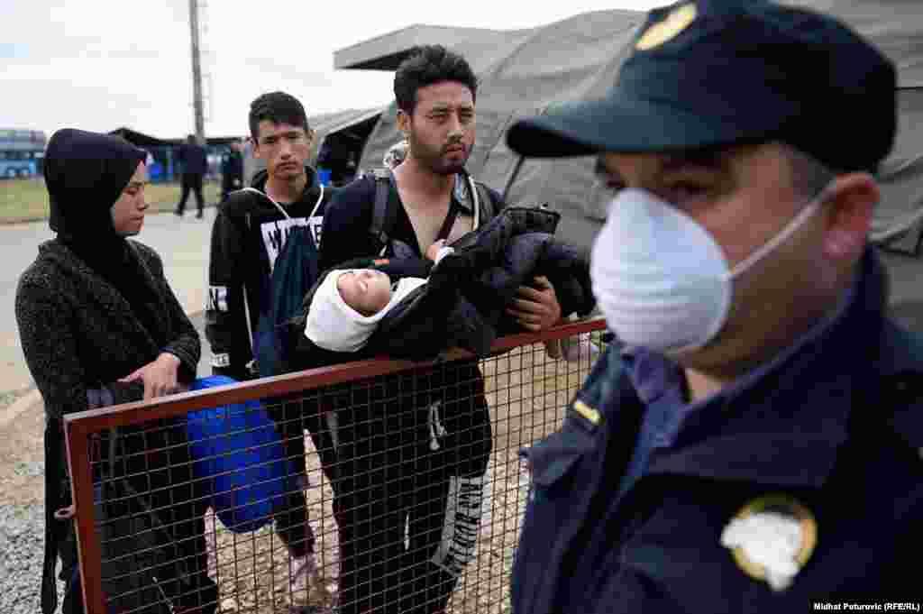 Čovjek drži dijete u naručju dok stoji u redu ispred šatora u prihvatnom centru u Opatovcu, pored grada Tovarnik u Hrvatskoj. Ovdje policija vrši registraciju izbjeglica sa Bliskog istoka.Nakon registracije izbjeglice nastavljaju put prema Sloveniji, većina izbjeglica želi da stigne u Njemačku.