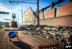 Робітники ремонтують лінію електропередач біля стіни місцевого цинкового заводу, який був пошкоджений в результаті ударної хвилі від вибуху метеорита.
