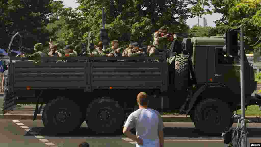 A military truck with heavily armed pro-Russian militants drives through a police checkpoint toward the airport of the eastern city of Donetsk.