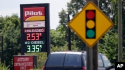 In this photo taken Thursday, June 14, 2018 an automobile drives past signage displaying gas prices at a Pilot gas station near Graham, N.C.