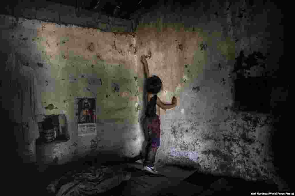 """Itzel Martinez, the photographer's daughter, plays inside her grandparents' house in Santiago Temixco, Mexico. Three of her uncles disappeared in 2013. More than 37,000 people have been categorized as """"missing"""" in Mexico by official sources. The vast majority of those are believed to be dead -- victims of ongoing violence that has claimed more than 250,000 lives since 2006. Long Term Projects: Second Prize - Yael Martinez"""