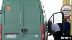 Një zyrtar i Doganave të Kosovës, duke kontrolluar një veturë në pikë kalimin kufitar në Merdare. Fotografi nga arkivi.