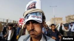 Участник демонстрации в Йемене несет на голове фотопортрет шиитского проповедника Нимра ан-Нимра. 18 мая 2015 года.
