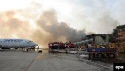 Дым над терминалом аэропорта в Карачи, на который было совершено вооруженное нападение, 9 июня 2014 года.
