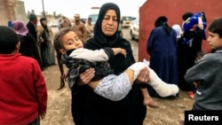 A displaced Iraqi woman who just fled her home carries her injured daughter as Iraqi forces battled Islamic State militants in western Mosul on March 2.