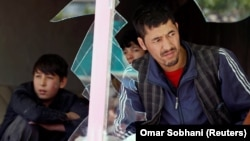 Afghan men look out through a broken window at the site of a suicide attack in Kabul on April 22.