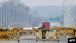 Северокорейский солдат стоит рядом с ограждениями, преграждающими путь в экономическую зону Кэсон. 24 апреля 2013 года.