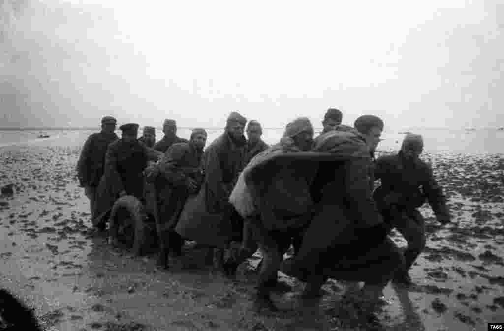 After the German defeat at Stalingrad in February 1943, the tide on the Soviet-German front began to shift. In late 1943, the Soviets prepared to retake Crimea by a combined assault across the Kerch Strait and down the Perekop Isthmus. The Soviets forced German prisoners of war to build walkways through the shallow Syvash Sea to enable Red Army forces to support the attack on the isthmus. By April 1944, the Germans had been pushed back into Sevastopol and the Red Army began its assault on the port. (Soviet soldiers crossing the Syvash Sea into Crimea in late 1943)