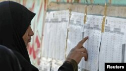 A woman checks candidate lists for the March 7 parliamentary elections at a polling station in Al-Basrah on March 3.