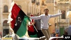 Либиски бунтовник го вее старото монархистичко знаме во Бенгази. Бунтовниците го прифатија старото знаме на либиската монархија.