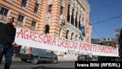 "A sign saying ""Serbia, An Aggressor, Needs To Be Punished"" is seen in front of City Hall in Sarajevo on February 17."