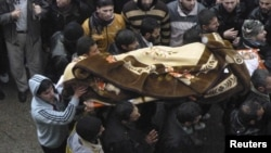 Syrian antigovernment protesters on January 29 carry a body during the funeral of a protester killed in earlier clashes in Baba Amro.