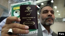 Iran - a man holds his passport in his hand . UNDATED