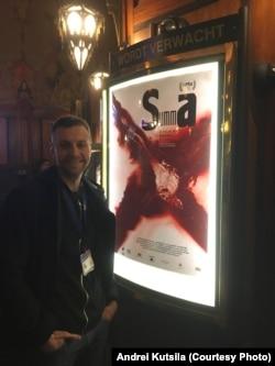 Андрэй Куціла на фоне афішы свайго фільму