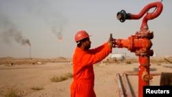 Нефтяник на трубопроводе близ нефтеперерабатывающего завода в иракском городе Ан-Наджафе.