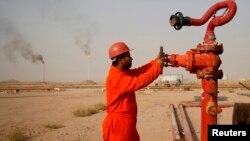 Нефтяник на трубопроводе близ нефтеперерабатывающего завода в иракском городе Ан-Наджафе