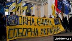 Учасники маршу ультрас, футбольних уболівальників та представників патріотичних організацій тримають полотно з написом «Одна, єдина, соборна Україна», Одеса, 5 березня 2016 року
