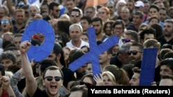Демонстранти тримають листи зі словом «ні» (OXI) під час мітингу в Афінах. 3 липня 2015 року