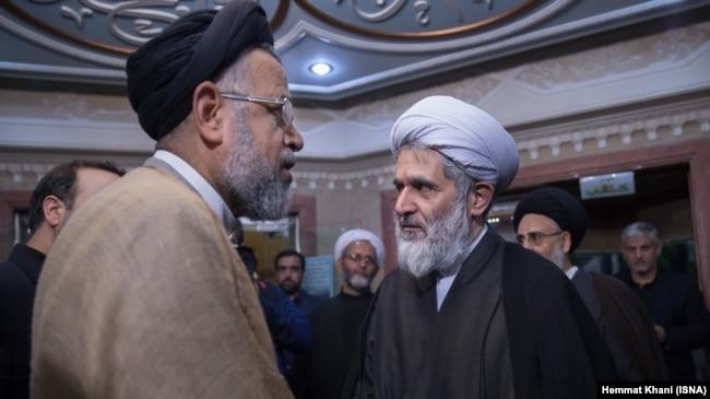 محمود علوی در حال گفتوگو با طائب در مراسم ختم پدر همسرش