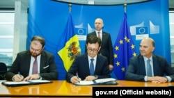 Guvernatorul BNM, Sergiu Cioclea, ministrul finanțelor, Octavian Armașu, eurocomisarul Pierre Moscovici (de la stânga la dreapta) și premierul Pavel Filip (în spate), în timpul semnării memorandumului la Bruxelles