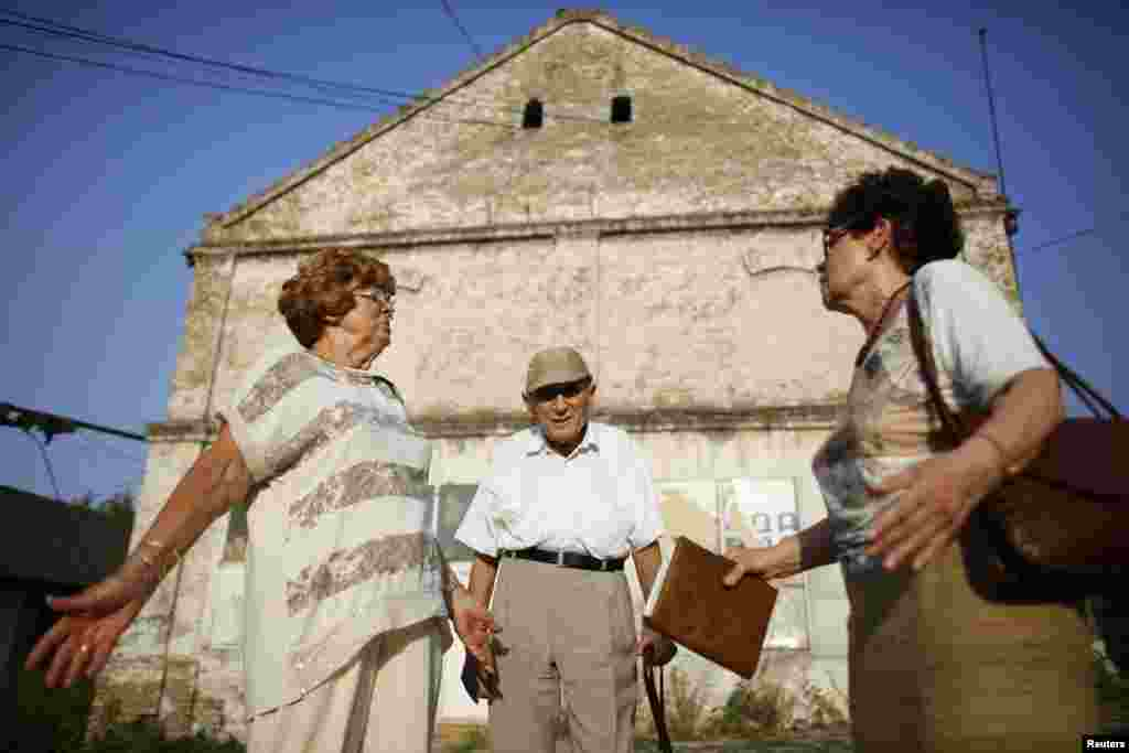 Lucija Rajner (left), Marijana Sibinovic, and Teodor Kovac at the site where their fathers were interned during World War II. Many people have expressed anger at the development plans for the former camp.