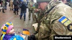 Дівчинка спілкується з бійцем-добровольцем батальйону «Київ-12» (архівне фото)