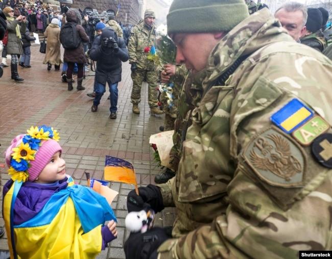 Дівчинка спілкується з бійцем-добровольцем батальйону «Київ-12». Столиця України, 6 грудня 2014 року