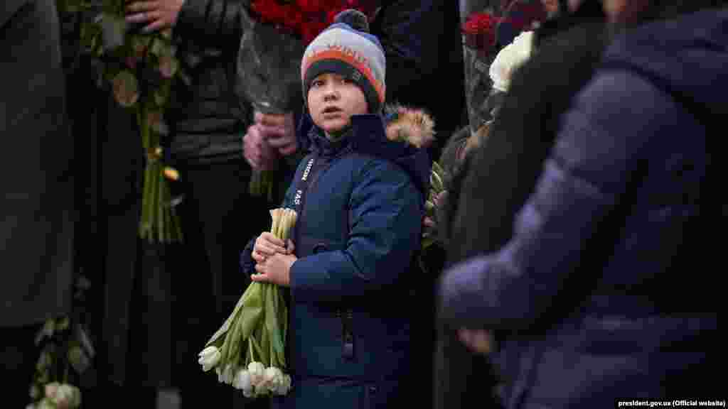 A young boy holds flowers during the memorial service at Boryspil airport.