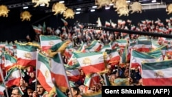 Mujahedin-e Khalq members wave Iranian flags during a conference in Albania in July 2019.