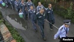 Укук коргоо кызматкери соттолуучуларды алып баратат. Кытай, 27-сентябрь, 2012-жыл