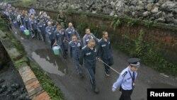 Полицейский ведет заключенных. Китай, 27 сентября 2012 года.