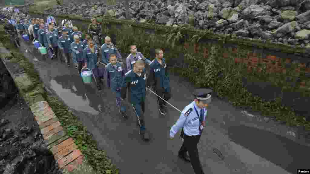 A Chinese policeman leads prisoners along a road in the Emei Mountain region, Sichuan Province,  on September 27. The inmates were being moved to a new prison. (REUTERS)