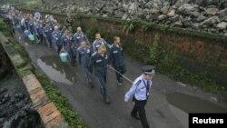 Китайский полицейский ведет привязанных друг к другу заключенных. Провинция Сичуан, 27 сентября 2012 года.