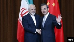 Chinese Foreign Minister Wang Yi (right) waves to photographers with his Iranian counterpart Javad Zarif in Beijing in 2015.
