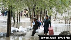 Afghan men carry their belongings as they evacuate from their residential area after flash flooding in the west of Kabul on April 16.
