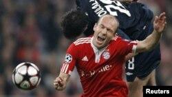 """""""Bavariya"""" yarim himoyachisi Aryen Robben """"Olimpik"""" (Lion) yarim himoyachisi Jeremi Tulalan bilan to'p uchun kurashmoqda. 21 aprel 2010 yil."""