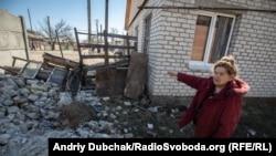 Валентина Олександрівна, мешканка Станиці Луганської, біля зруйнованого будинку свого сина