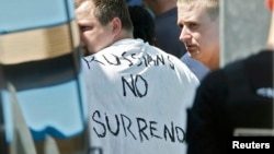 "Russian soccer fans suspected of being involved in clashes, with one wearing a banner saying ""Russia no surrender,"" are ushered off their bus after being stopped by gendarmes in Mandelieu near Cannes, France, on June 14."